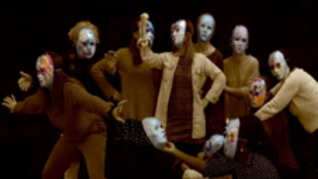 Photo of women wearing masks in a performance